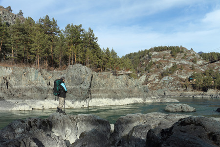 The traveler with a backpack and tracking sticks standing on a stone on the river bank among mountains looking at the destroyed suspension bridge photo