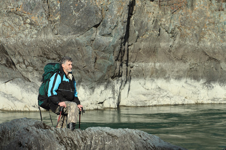 The traveler  with a backpack and tracking sticks going on the rocky bank of the mountain river photo