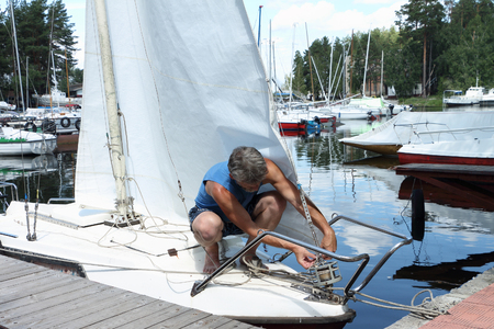 The man in a blue shirt  fixes staysail on a yacht nose at the mooring Stock Photo