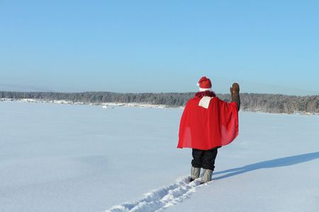 The man in Santa Clauss suit going on a snow field against the sky photo