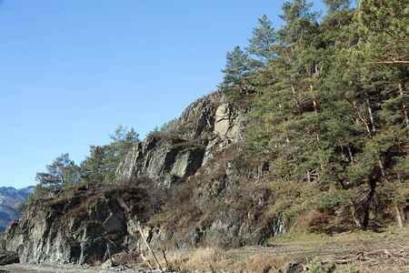 abrupt: Rocky slope of the mountain against the blue sky in clear day. Altai
