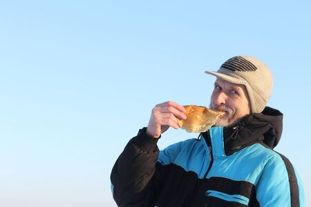 shrove: The man in a black jacket  eating  pancake outdoors against the blue sky