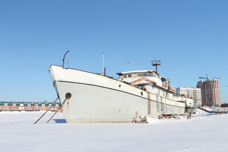 held down: Decommissioned river vessel standing on the river which is held down by ice in harbor in the winter Stock Photo