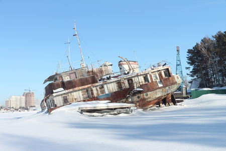 superstructure: Afterpart of the decommissioned dry-cargo ship in harbor on the river in the winter