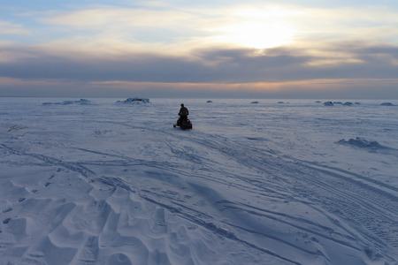undulate: The person going on a snowmobile on the frozen river in the winter at sunset Stock Photo
