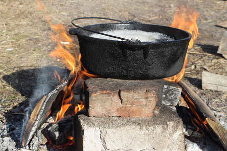 fire bricks: The food in the cast-iron cauldron standing on bricks is cooked on fire outdoors
