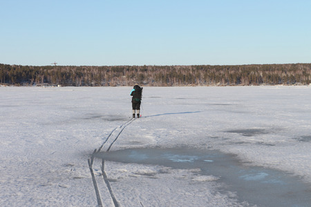 gaiters: The man the traveler with a backpack going on skis on the thawing river in the spring