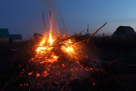 scorching: Night fire in the distance from houses against the sky in the village