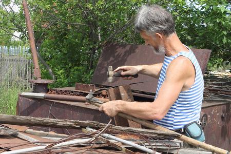 guada�a: El hombre le pega fuera guada�a un martillo en un jard�n