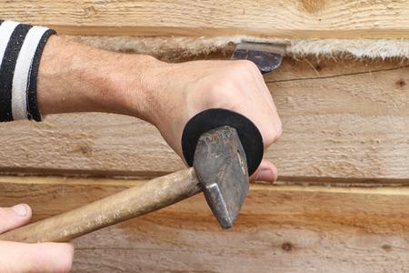 caulk: Male hands caulk a house wall from a bar Stock Photo