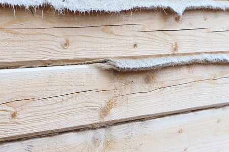 profiled: House wall with a heater layer put from a fresh pine bar outdoors