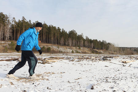 one senior adult man: The man in a blue jacket running on snow on the river bank Stock Photo