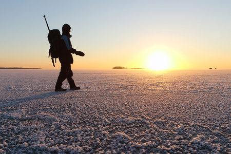 nonuniform: The man with a backpack going on ice on the river at sunset in the fall. River Ob, Russia