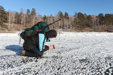 nonuniform: The man with the camera in a hand removes a snow background on the frozen river