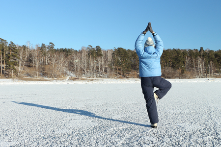 winter sports: The woman in a blue jacket practicing yoga on a snow-covered surface of the river in the fall Stock Photo