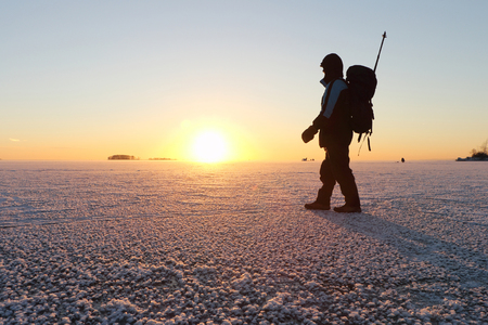 heterogeneous: The man with a backpack going on ice on the river at sunset in the fall. River Ob, Russia