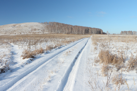 novosibirsk: Snow automobile road  going near a hill Bald, Bugotaksky hills, the Novosibirsk region, Russia