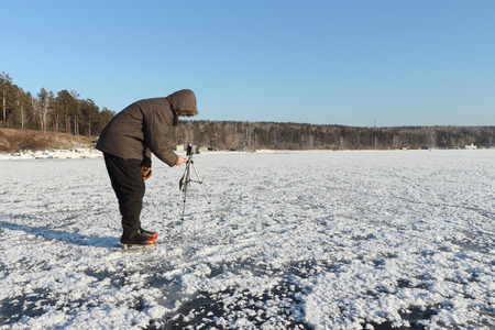 heterogeneous: The man on the skates with a camera on a support photographing a surface of the frozen river