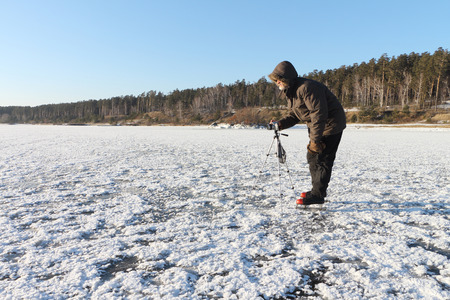 nonuniform: The man on the skates with a camera on a support photographing a surface of the frozen river