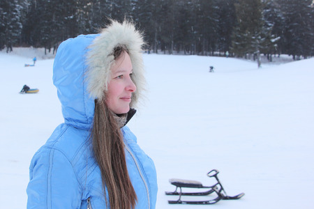 upper half: The beautiful woman with long hair in a blue jacket with a hood against snow and the wood in the winter