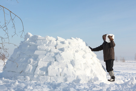 The man building an igloo on a snow glade in the winter