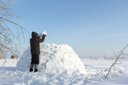 hobby hut: The man  building an igloo on a snow glade in the winter