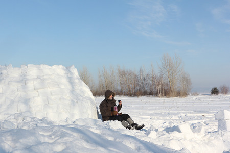 thermos: The man sitting near an igloo and drinking tea from thermos  in the winter