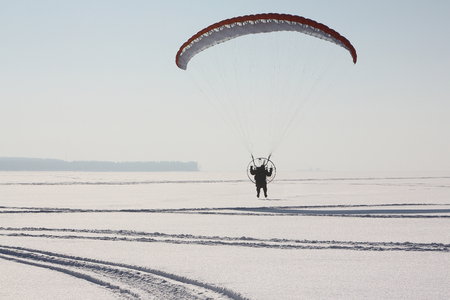 motorized: The flying-up person on a motorized paraglider against a snow surface of the river