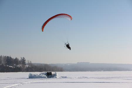 MOTORIZADO: La persona volando en un paraplane motorizada contra la superficie de la nieve del río Foto de archivo