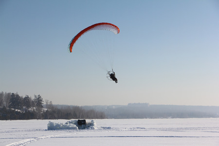 motorized: The person flying on a motorized paraplane against the snow surface of the river Stock Photo