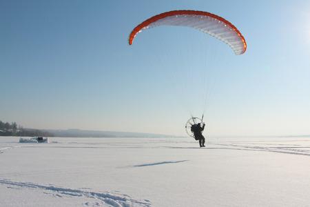 motorizado: La persona volando arriba en un parapente motorizado contra una superficie de la nieve del r�o
