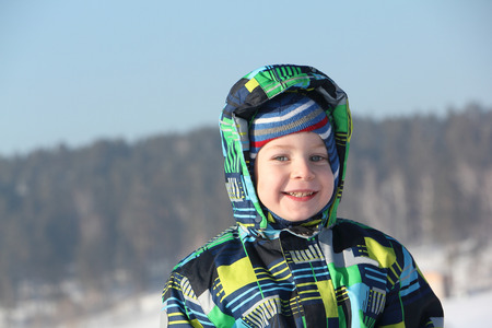 perky: The happy child in a color jacket with a hood against the sky and snow
