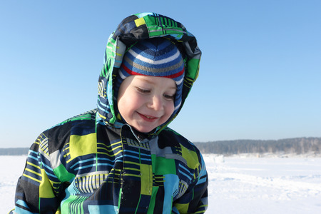 perky: The smiling child in a color jacket with a hood against snow in the winter