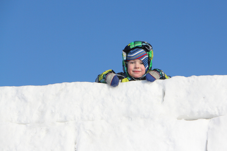 upper half: The little boy in a color jacket with a hood at wall top from snow blocks Stock Photo
