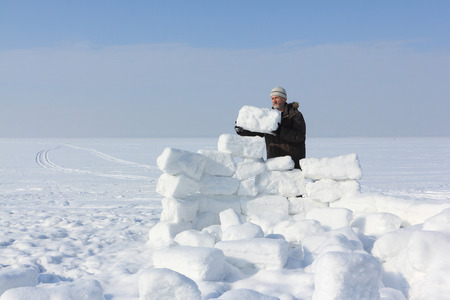 gaiters: The man with a beard in a gray cap building an igloo of snow blocks  on a glade in the winter
