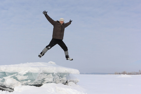 gaiters: The man with a beard in a gray cap jumping from an block of ice in the snow