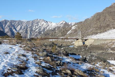 katun: Suspension bridge Oroktoysky through the frozen Katun  river among mountains, Altai, Russia