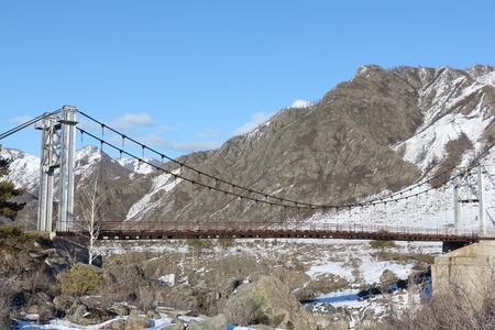 Suspension bridge Oroktoysky through the frozen Katun  river among mountains, Altai, Russia
