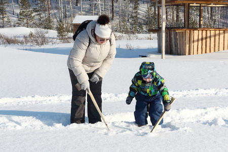 perky: The woman and the kid in a color jacket drawing sticks on snow in the winter