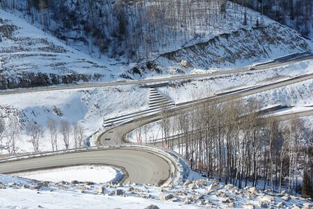 lacet: Mountain highway among snow slope, Belokurikha, Altai, Russia Stock Photo