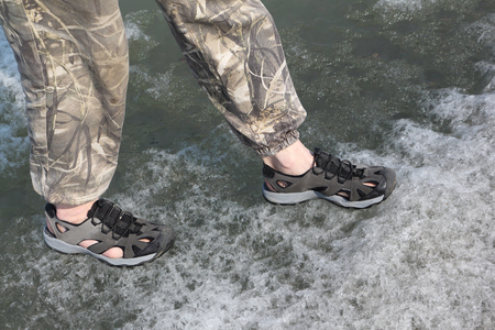 thawing: Male legs in sandals for rafting on ice of the thawing river
