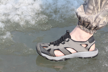 thawing: Male leg in sandals for rafting on ice of the thawing river
