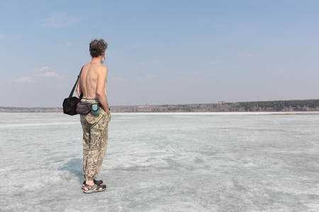 nonuniform: The gray-haired man with bare torso standing on ice of the thawing river in the spring Stock Photo