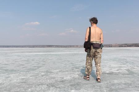 春の融解の川の氷の上行く裸の胴体と白髪の男