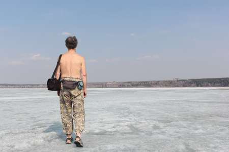nonuniform: The gray-haired man with a bare torso going on ice of the thawing river in the spring