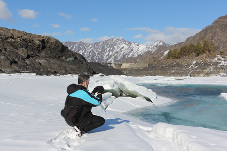 thawing: The elderly man with a beard photographing the thawing river among mountains in the spring,  Russia, Altai, the river Katun
