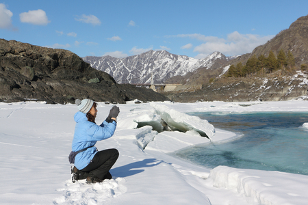 thawing: The woman in a blue jacket photographing the thawing river among mountains in the spring, Russia, Altai, the river Katun