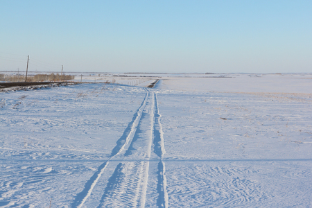 rut: Trace from a snowmobile among a snow field in rural areas Stock Photo