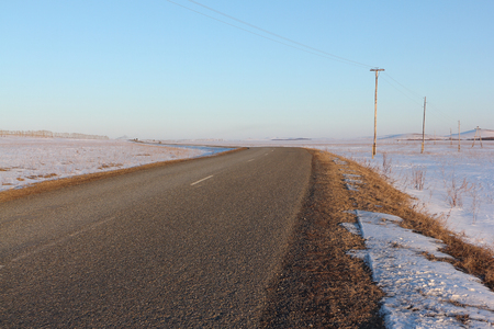 snow fields: The asphalt rural road going among snow fields Stock Photo