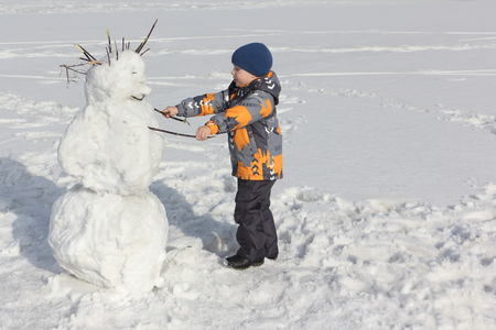 ittle: The little boy in a color jacket building a snowman in the winter